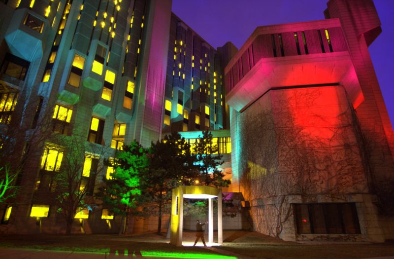 Photograph of Robarts libary, where the ATRC is located - the towering concrete and glass walls are lit with multi-coloured lights